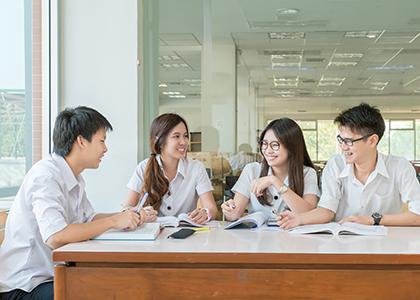 4人の学生が笑顔で勉強をしている