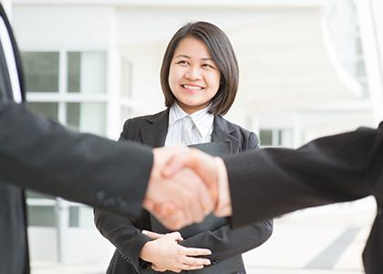 女性が笑顔で握手を交わしている人たちを見ている